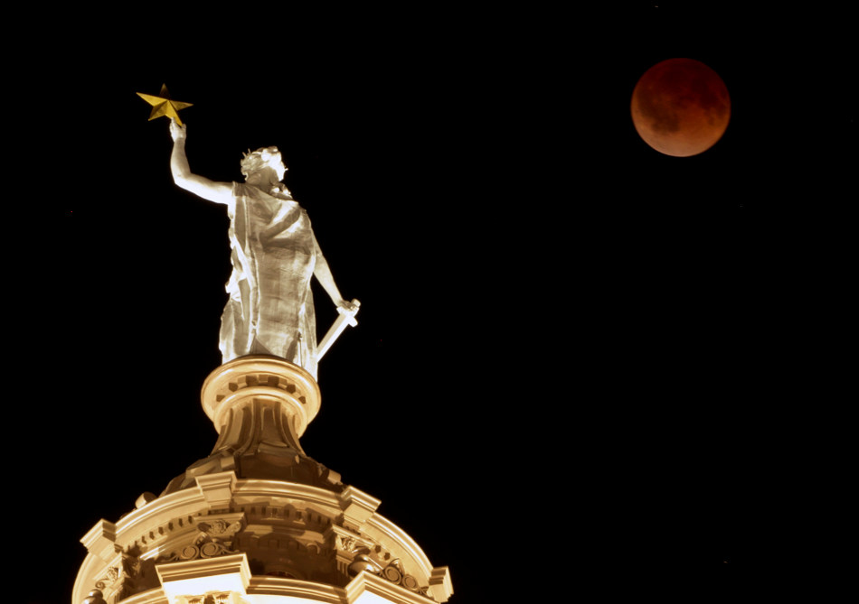 The moon glows a red hue over the Goddess of Liberty statue atop the Capitol in Austin, Texas, during a total lunar eclipse Tuesday, April 15, 2014. Tuesday's eclipse is the first of four total lunar eclipses that will take place between 2014 to 2015. (AP Photo/Austin American-Statesman, Jay Janner) AUSTIN CHRONICLE OUT, COMMUNITY IMPACT OUT, INTERNET AND TV MUST CREDIT PHOTOGRAPHER AND STATESMAN.COM, MAGS OUT