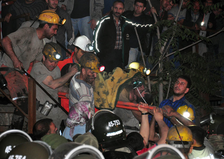 Miners carry a rescued friend after an explosion and fire at a coal mine killed at least 17 miners and left up to 300 workers trapped underground, in Soma, in western Turkey, Tuesday, May 13, 2014, a Turkish official said. Twenty people were rescued from the mine but one later died in the hospital, Soma administrator Mehmet Bahattin Atci told reporters. The town is 250 kilometers (155 miles) south of Istanbul. The death toll was expected to rise.(AP Photo/IHA) TURKEY OUT