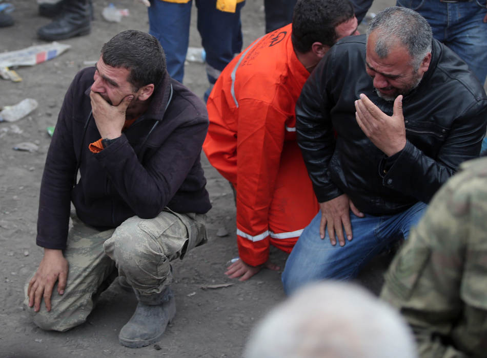 Family members, react, as they wait outside the mine in Soma, western Turkey, Wednesday, May 14, 2014. Rescuers desperately raced against time to reach more than 200 miners trapped underground Wednesday after an explosion and fire at a coal mine in western Turkey killed at least 200 workers, authorities said, in one of the worst mining disasters in Turkish history. Turkey's Energy Minister Taner Yildiz said 787 people were inside the coal mine in Soma, some 250 kilometers (155 miles) south of Istanbul, at the time of the accident and 363 of them had been rescued so far. (AP Photo/Emrah Gurel)