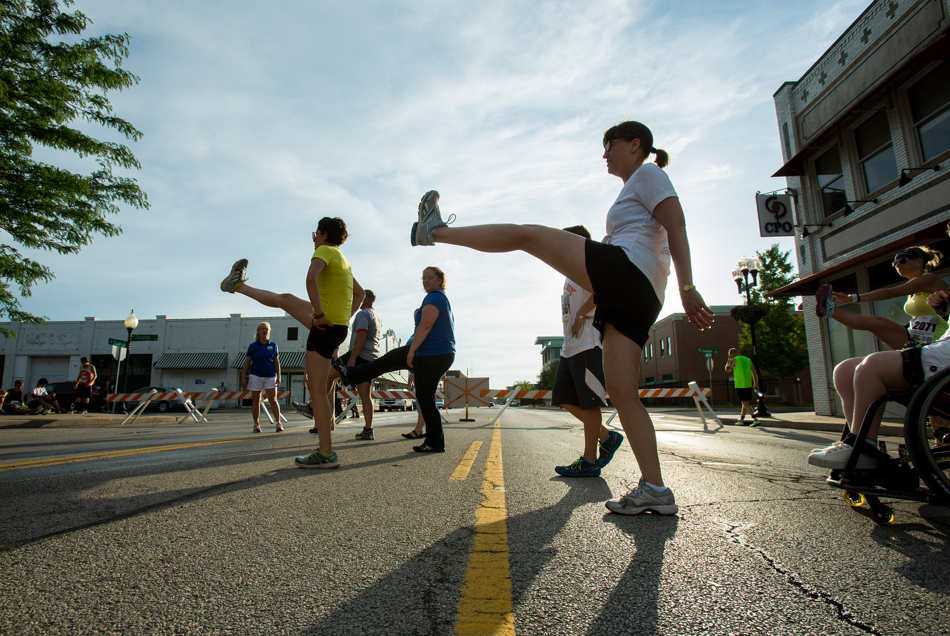 TING SHEN/JOURNAL STAR  Runners stretch out Friday, June 27 before the second wave of the Main Street Mile in downtown Peoria.