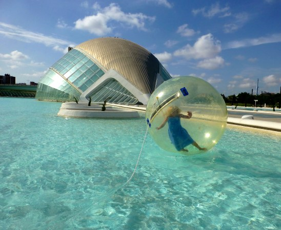 Blonde woman floating in a bubble at the City of Arts and Sciences Valencia Spain