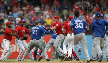 ARLINGTON, TX - MAY 15:  The Toronto Blue Jays and the Texas Rangers clear the bench after Jose Bautista #19 of the Toronto Blue Jays was punched by Rougned Odor #12 of the Texas Rangers in the eighth inning at Globe Life Park in Arlington on May 15, 2016 in Arlington, Texas.  (Photo by Ronald Martinez/Getty Images)