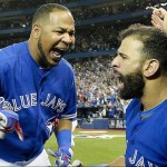 Toronto Blue Jays' Edwin Encarnacion, left, reacts with Blue Jays right fielder Jose Bautista, right, after hitting a solo home run against the Texas Rangers during the sixth inning in Game 5 of baseball's American League Division Series, Wednesday, Oct. 14, 2015 in Toronto. The Toronto Blues Jays beat the Texas Rangers 6-3. (Nathan Denette/The Canadian Press via AP) MANDATORY CREDIT