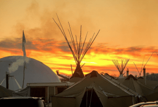 The sun sets over the Oceti Sakowin camp at Standing Rock 12/4/16. Photo by Paul Hebert (@PaulHebertPhoto). Used with permission.