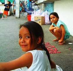 Little girls in Mexico playing with bottle caps.