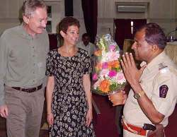 Street crime in Mumbai, India: Senior Police Inspector Bhawale presents Bob Arno and Bambi with a thank-you bouquet.