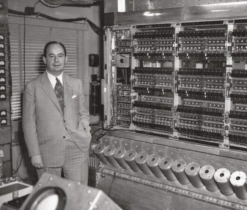 John von Neumann standing in front of machine