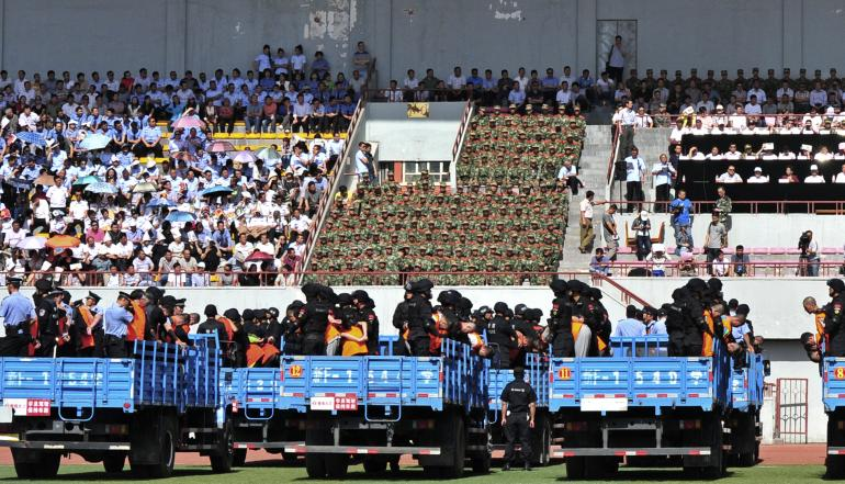 "Trucks carrying criminals and suspects are seen during a mass sentencing rally at a stadium in Yili, Xinjiang Uighur Autonomous Region on May 27, 2014. Local officials in China's western Xinjiang region held the public rally for the mass sentencing of criminals on Tuesday, handing out judgments for 55 people and at least three death sentences for crimes such as ""violent terrorism,"" state media said. [Reuters]"