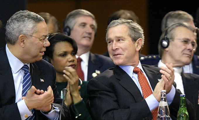 U.S. President George W. Bush and Secretary of State Colin Powell applaud at the North Atlantic Council Summit in Prague November 21, 2002.   Between them is Secretary of State Condoleezza Rice, to their right, Defense Secretary Donald Rumsfeld. [REUTERS/Kevin Lamarque]