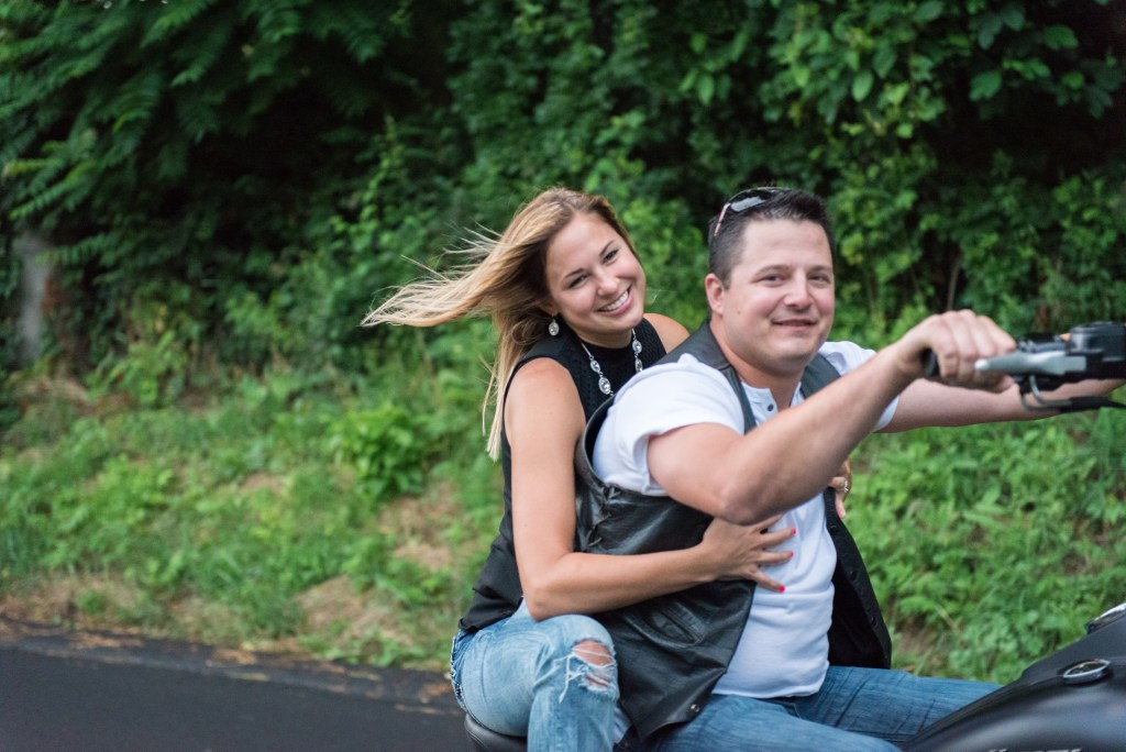 Couple riding harley down road engagement shoot