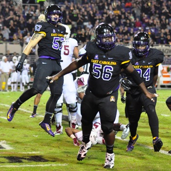 Defensive line stalwart Demetri McGill (56) and teammates showed their enthusiasm after a tackle-for-loss in a game last season. (File photo by W.A. Myatt)