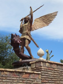 A statue of San Miguel slaying a serpent adorns the entry wall.