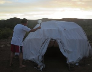 The spiritual healer purifies the temazcal hut with sage smoke prior to our beginning the traditional sweat lodge experience..