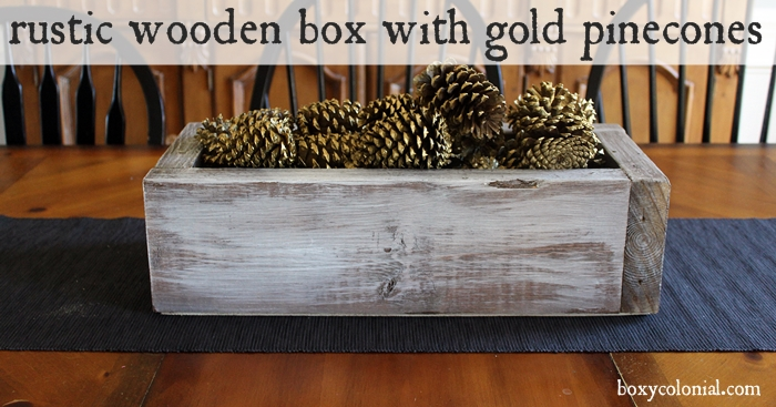 Rustic wooden box centerpiece with gold pinecones
