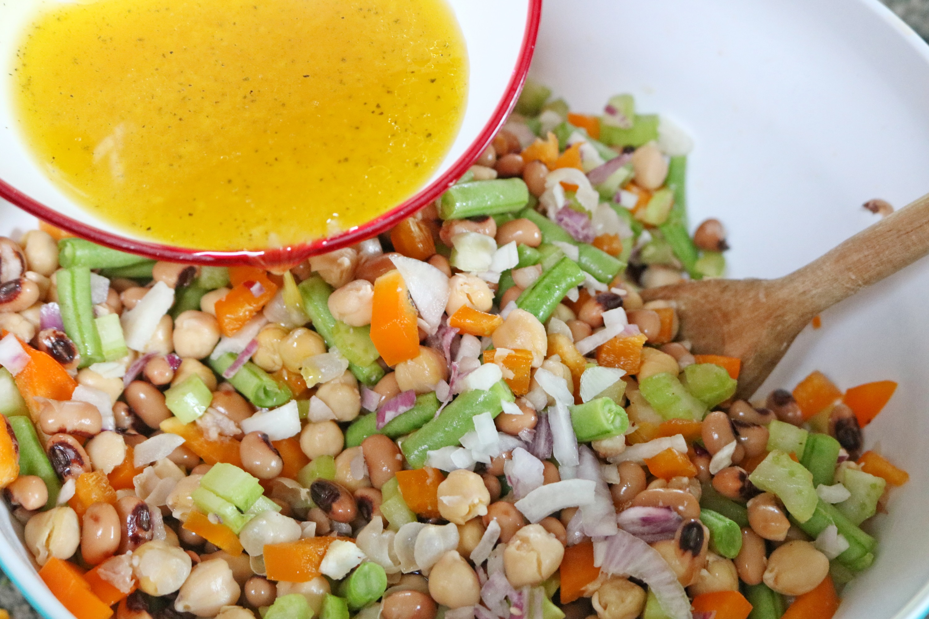 Pour the dressing over the bean salad and gently stir everything together until it's combined.