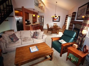 The living room has a sleeper sofa, TV, DVD, and gas fireplace. The unit has an open floor plan with vaulted ceilings.
