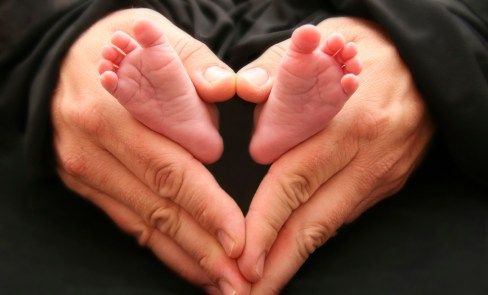 This is a photo of a dad with his hands in a heart shape holding his 3 week old infants feet. &quot;Heart feet&quot; is frequently used by pro-life organizations as a pro-life symbol.
