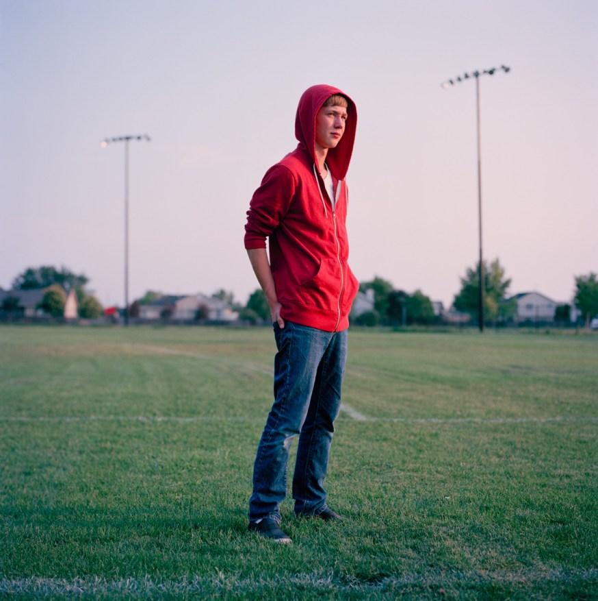 Portrait Photography NYC Teen boy red hoodie suburban park baseball field sunset Utah