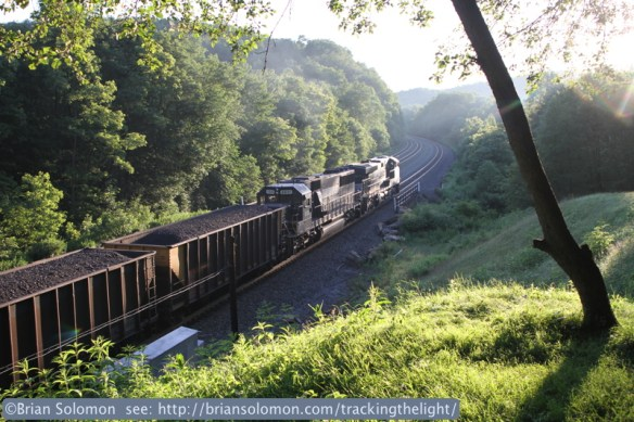 A Norfolk Southern coal train, likely destined for Pennsylvania Power & Light's Strawberry Ridge plant, works west at Cassandra, Pennsylvnia. Canon EOS 7D with 24mm lens, exposed at f4 1/250th second, ISO 200. Back lit morning sun highlights the grass in the foreground.