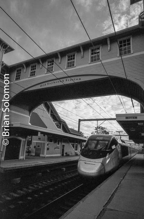 A New York bound Amtrak High Speed Train (working as an Acela service) blitzes the station at Old Saybrook, Connecticut. Exposed with a 21mm f4.0 Super Angulon. I exposed for the sky, allow other elements of the scene to remain in relative shadow.