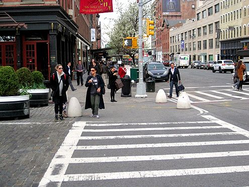 The bump outs at the intersection narrows the streets and shortens the distance for pedestrians to cross