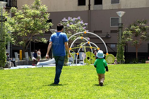 A father and son walk over to the new playground in the park