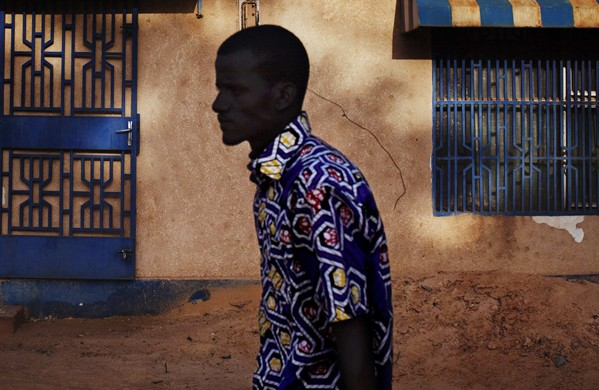 """A man walks past a sign reading """"Niger"""" in Niamey"""