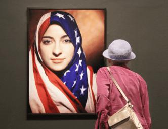 A NMWA visitor studies Boushra Almutawakel's Untitled from The Hijab series