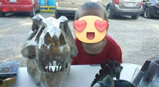 A young fair participant has picture with T-Rex model.
