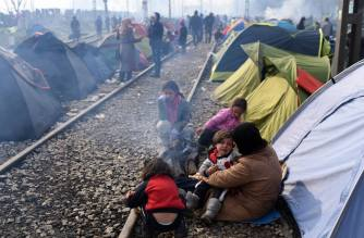 Refugees from Mideast wars camped along rail lines in Greece.