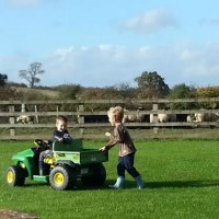 cousins playing with John Deere gator