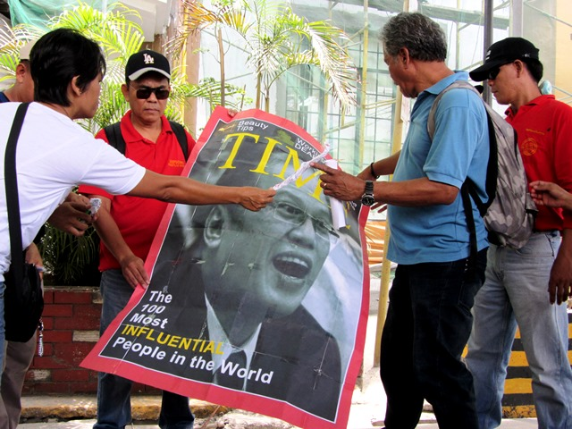 Union leaders bring in front of labor department a spoof of Time magazine cover citing Pres. Aquino as one of 100 'most influential persons.'