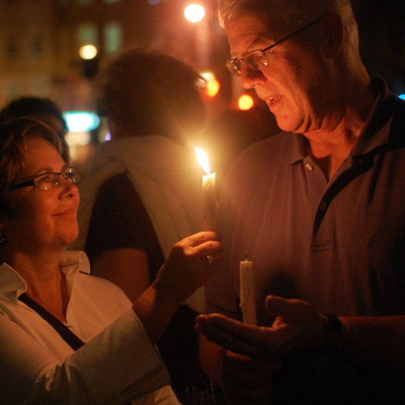 A couple blows each other's candles out at the end of the vigil