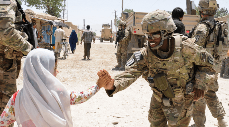 A female soldier high-fives a young girl in Afghanistan. Female soldiers play an essential role in warfare, especially in Iraq and Afghanistan. Photo by DVIDSHUB ? the Flickr Commons