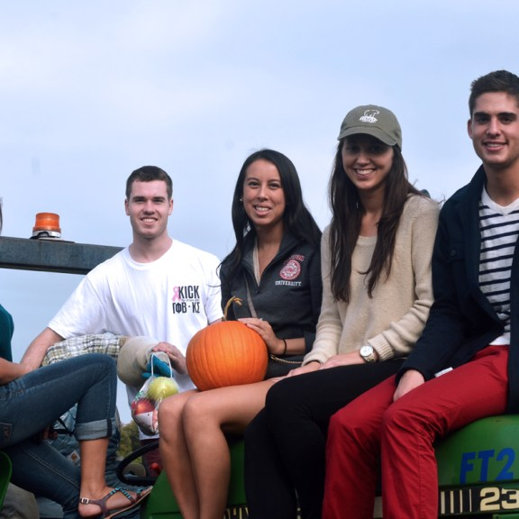 Seniors Bobby Patrovic (CAS), Jackie Leiser (CAS), Daniela DeConti (CAS), Eric Bancroft (ENG), and Brittany Gldsborough (CAS) rest on a tractor after a fun day of apple picking!