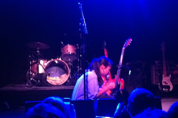 "Mitski unorthodoxly strumming her guitar in its stand while wrenching hearts during ""Class of 2013."""