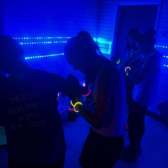 First on the agenda at Glow Yoga is a stop at the glow paint table to get a touch of neon color before class starts. | Photo by Olivia Drago