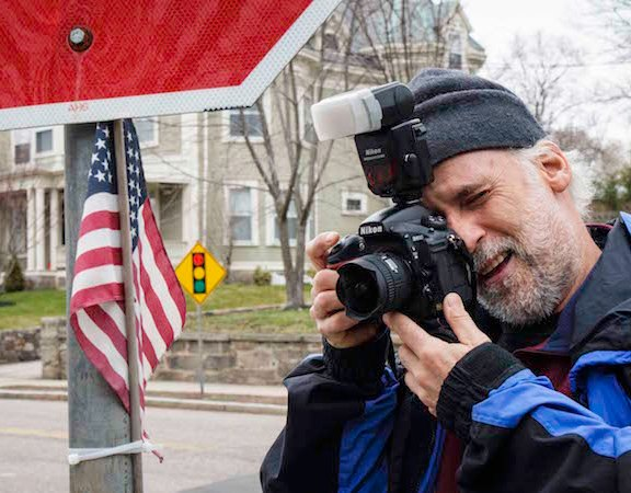 Touster photographs the American flag that hangs on the street sign at Franklin Street in Watertown.
