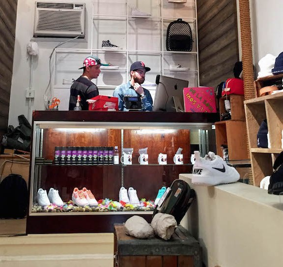 The industrial-looking modern sales counter behind the secret doorway separating the bodega from the shoe store bears no resemblance to the messy looking storefront that customers enter first. | Photo by Siena Tauber