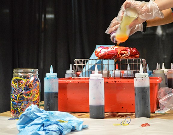 A students dips a t-shirt in dye.