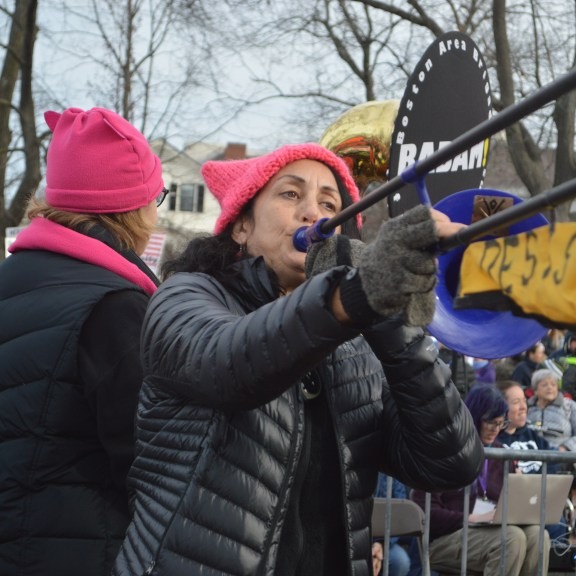 A BAMAM musician plays a trombone with a flag hanging that says 'resist'. Photo by Carolyn Komatsoulis