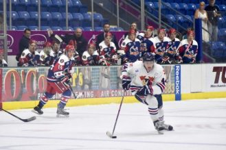 Brendan White carries the puck up the ice.