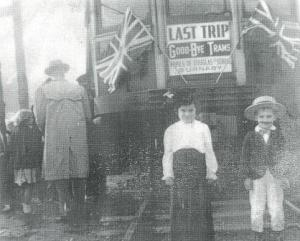 """Two children stand in front of the Burnaby Lake Interurban car, just prior to its last run through Burnaby in 1953. The boy has been identified as Grant Washington. A sign attached to the car reads: """"Last trip, good-bye trams, Pupils of Douglas School, Burnaby."""" (Item 431-001, from the Burnaby Historical Society Community Archives Collection, courtesy of the City of Burnaby Archives.)"""