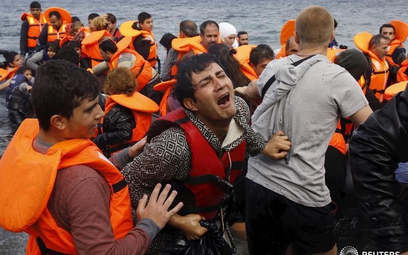 A Syrian refugee cries while disembarking from a flooded raft at a beach on the Greek island of Lesbos, after crossing a part of the Aegean Sea from the Turkish coast on an overcrowded raft, October 20, 2015. Thousands of refugees - mostly fleeing war-torn Syria, Afghanistan and Iraq - attempt daily to cross the Aegean Sea from nearby Turkey, a short trip but a perilous one in the inflatable boats the migrants use, often in rough seas. Almost 400,000 people have arrived in Greece this year, according to the U.N. refugee agency UNHCR, overwhelming the cash-strapped nation's ability to cope. REUTERS/Yannis Behrakis - RTS5AAI