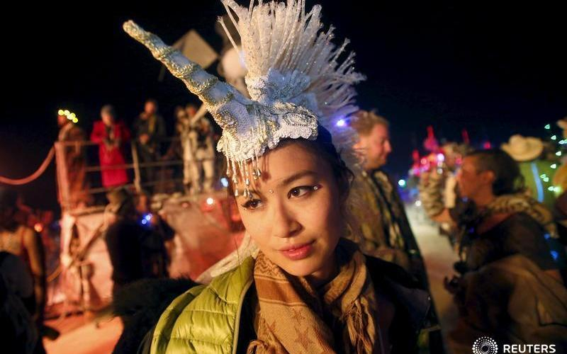 "Sarah Tang wears a unicorn head piece as she dances during the Burning Man 2015 ""Carnival of Mirrors"" arts and music festival in the Black Rock Desert of Nevada, September 5, 2015. Approximately 70,000 people have come to the sold-out festival that ends Sunday evening. REUTERS/Jim Urquhart  FOR USE WITH BURNING MAN RELATED REPORTING ONLY. FOR EDITORIAL USE ONLY. NOT FOR SALE FOR MARKETING OR ADVERTISING CAMPAIGNS. NO THIRD PARTY SALES. NOT FOR USE BY REUTERS THIRD PARTY DISTRIBUTORS - RTX1RAT4"