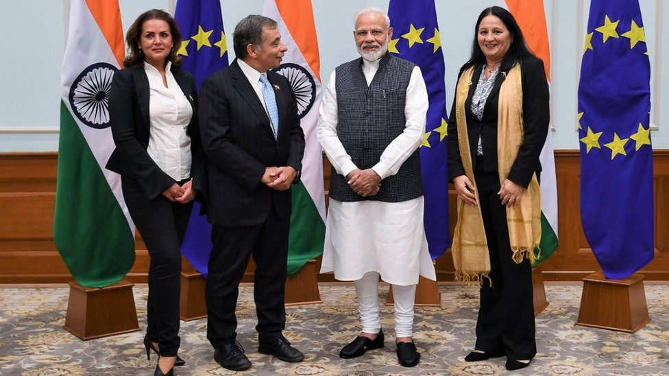 Delegation pose for picture in front of flags