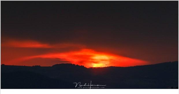 Het einde van de dag, als de zon achter de wolken vandaan komt en de horizon aanraakt.