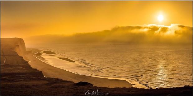 Een onwerkelijk wereld door het zonlicht in de vreemde gele lucht terwijl de mist over de zee heen steeds dichterbij komt (EF70-200L II @ 70mm | ISO100 | f/8 | | panorama van drie opnamen)