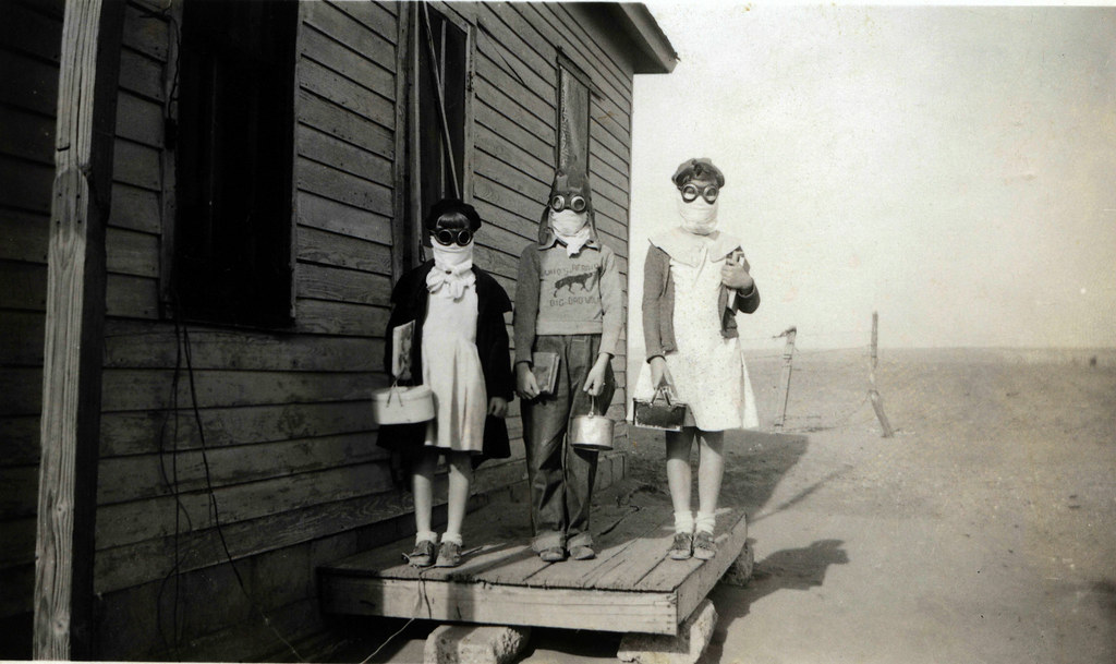 Three children prepare to leave for school wearing goggles and homemade dust masks to protect them from the dust. Lakin, Kansas, 1935. Credit: Green Family Collection