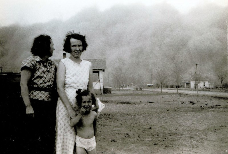 As a black blizzard rolls in to Ulysses, Kansas, two women and a girl pose for a photograph before taking shelter.